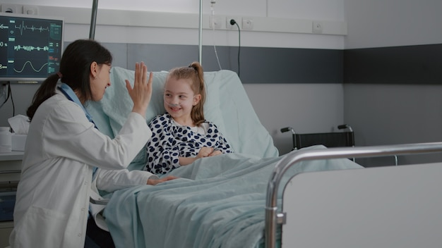 Médica pediátrica interagindo com paciente doente dando high five durante consulta clínica