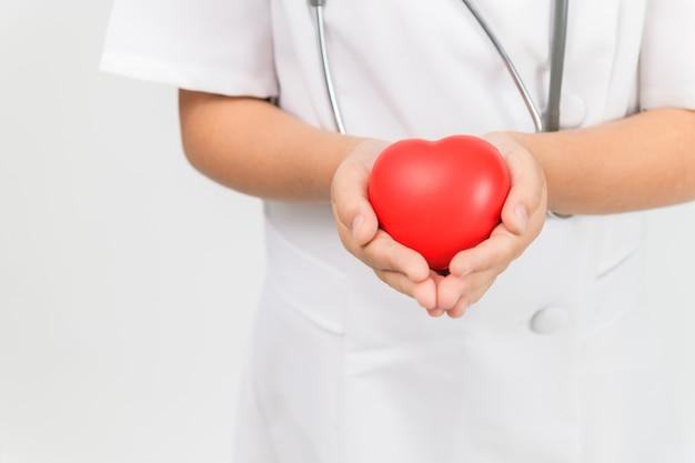 Médica pequena com estetoscópio segurando coração