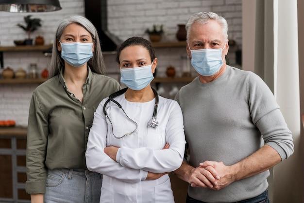 Médica posando com seus pacientes atrás