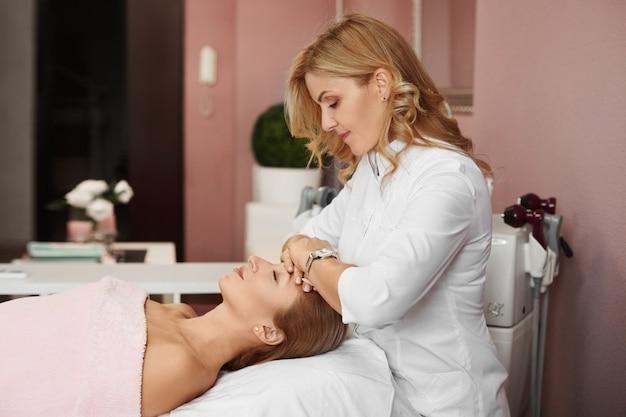 Médica, preparando uma jovem para o procedimento não cirúrgico de lifting facial. um tratamento cosmético rejuvenescedor na clínica de medicina estética.