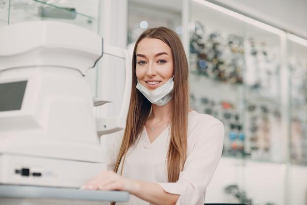Médica profissional com máscara facial usando equipamento eletrônico digital moderno para teste ocular, verificando a visão