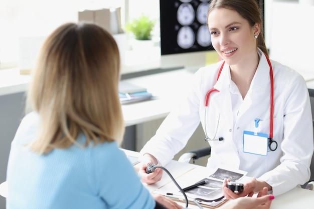 Médica que mede a pressão arterial do paciente na clínica