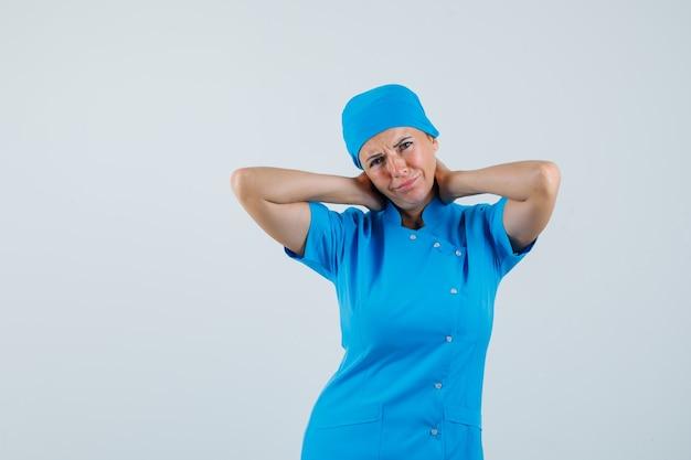 Médica que sofre de dores no pescoço, com uniforme azul e parece desconfortável. vista frontal.
