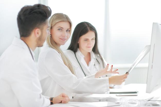 Médica radiologista mostrando um raio-x para seus colegas
