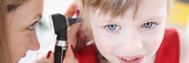 Médica realiza exame de orelha de menina