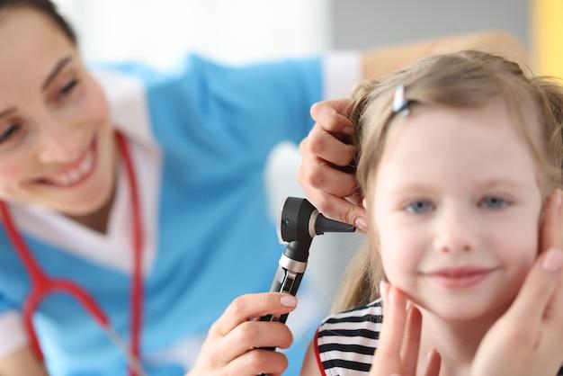 Médica realiza exame médico do ouvido com um otoscópio para a menina