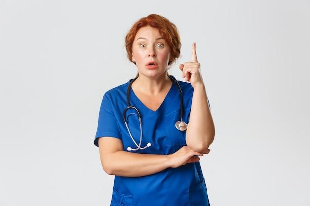 Médica ruiva oprimida, enfermeira de meia-idade em uniforme tem sugestões, dizendo ideia ou plano, erguendo o dedo indicador eureka, gesto com expressão preocupada
