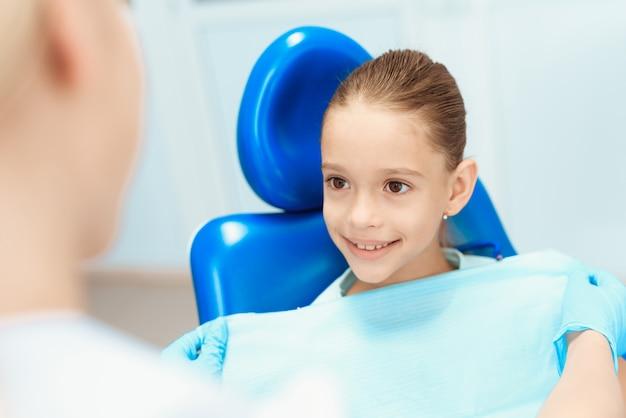 Médica se preparando para examinar os dentes de uma menina