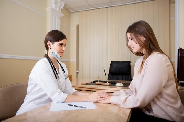 Médica segura as mãos do paciente, relatando os resultados dos testes.