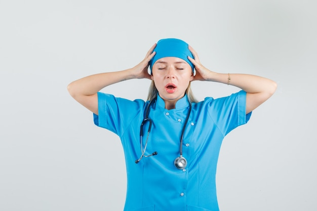Médica, segurando a cabeça com as mãos em uniforme azul e parecendo exausta.
