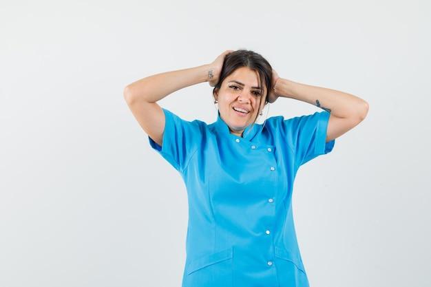 Médica segurando a cabeça com as mãos no uniforme azul e bonita