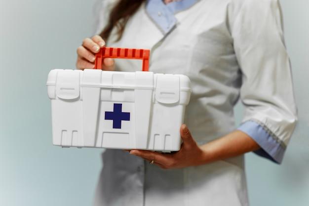 Médica, segurando a caixa de primeiros socorros no hospital