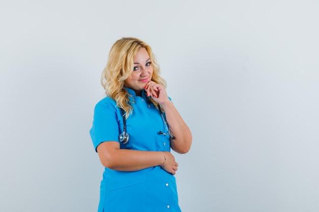 Médica segurando a mão no queixo com uniforme azul e olhando para o espaço otimista para texto