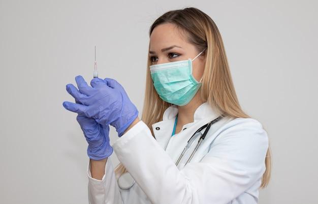 Médica, segurando a seringa com injeção