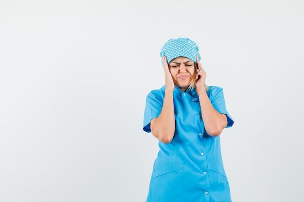 Médica segurando as mãos na cabeça com uniforme azul e parecendo doente