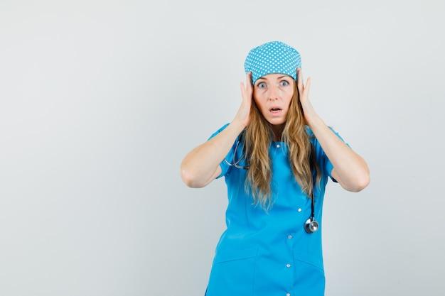Médica segurando as mãos na cabeça em uniforme azul e parecendo agitada.