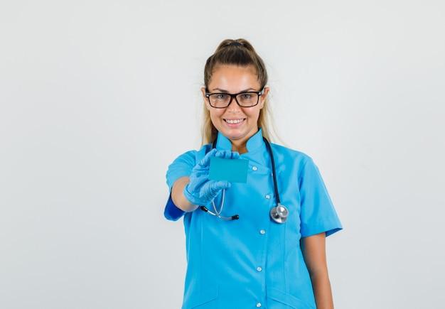 Médica segurando cartão com uniforme azul, luvas