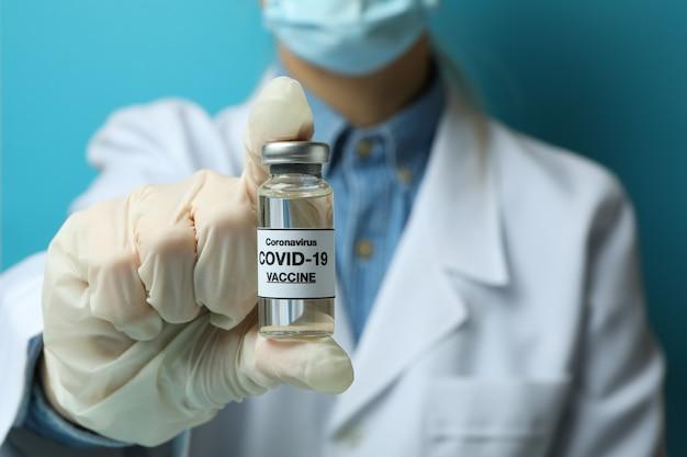 Médica segurando frasco com vacina covid - 19 em fundo azul