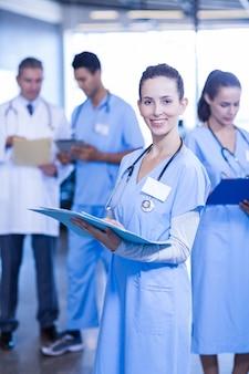 Médica, segurando o relatório médico e sorrindo enquanto seus colegas de pé