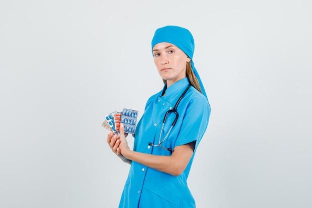 Médica segurando pacotes de comprimidos em uniforme azul e parecendo séria