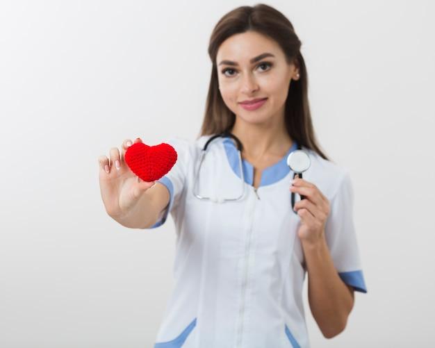 Médica, segurando um coração de pelúcia e um estetoscópio