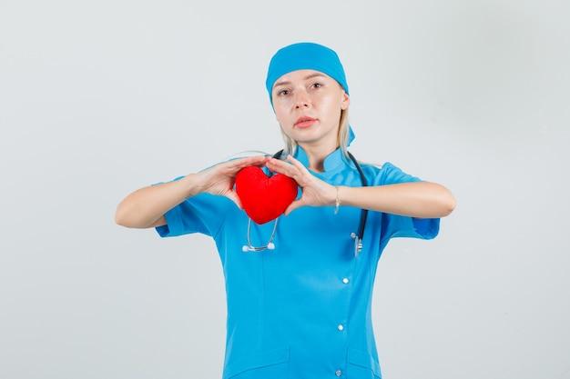 Médica segurando um coração vermelho em uniforme azul e olhando séria