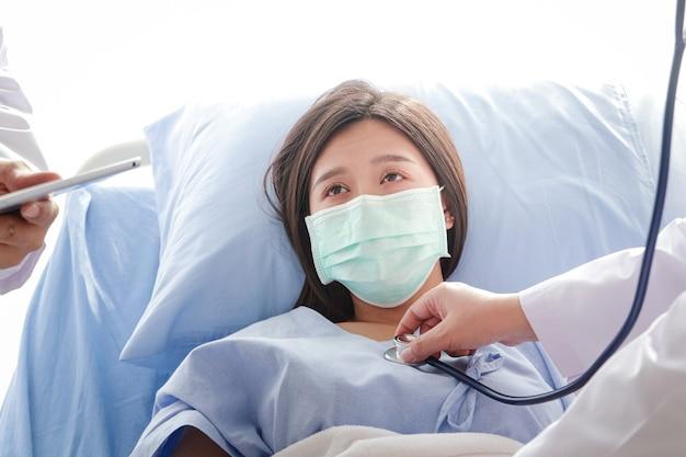 Médica segurando um estetoscópio, médica que examina o coração, paciente asiática use uma máscara azul e deite-se em uma cama de hospital. conceito de serviço médico, seguro saúde. copie o espaço
