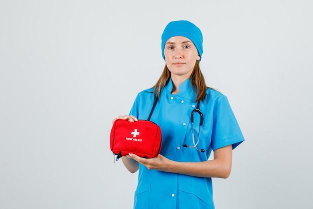 Médica segurando um kit de primeiros socorros de uniforme e olhando com cuidado