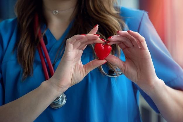 Médica segurando um pequeno coração vermelho, close-up