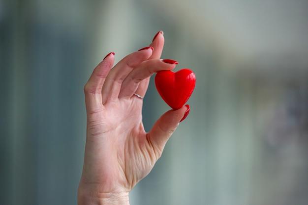 Médica segurando um pequeno coração vermelho