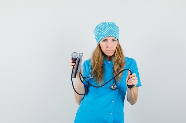Médica segurando uma braçadeira de pressão arterial em uniforme azul