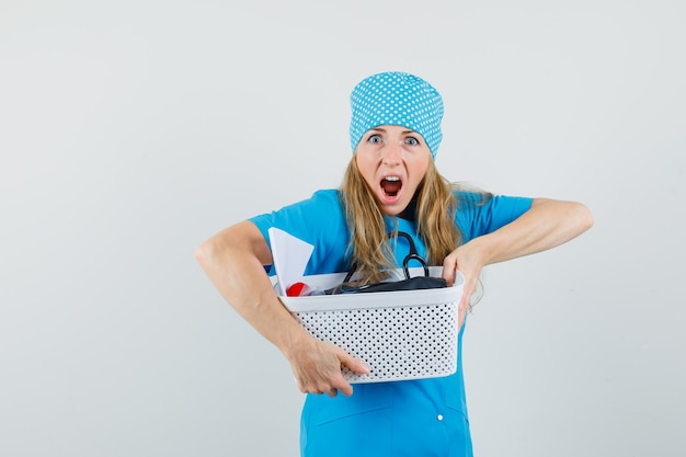 Médica segurando uma cesta com instalações médicas em uniforme azul e parecendo agitada