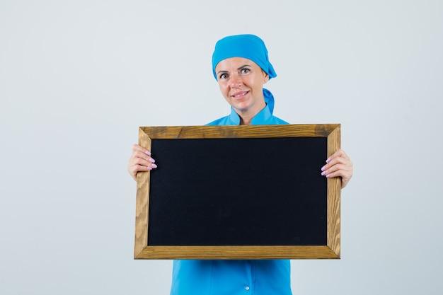 Médica segurando uma lousa em uniforme azul e olhando otimista, vista frontal.