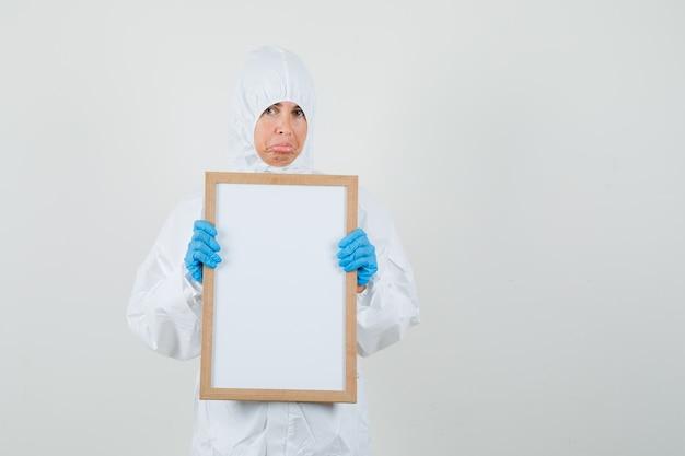 Médica segurando uma moldura em branco em um traje de proteção