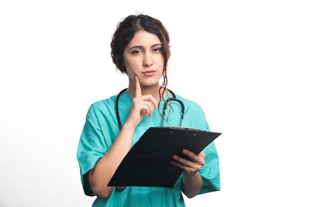 Médica segurando uma prancheta preta nas mãos, sobre fundo branco. foto de alta qualidade