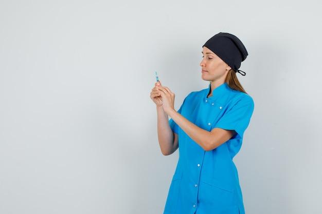 Médica segurando uma seringa para injeção em uniforme azul, chapéu preto e parecendo ocupada