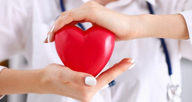 Médica segurar nos braços e cobrir o coração vermelho