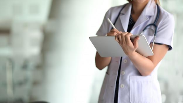 Médica segurar o tablet digital e escrever na tela de toque no escritório