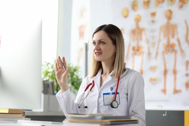 Médica sentada à mesa e acenando para a tela do computador