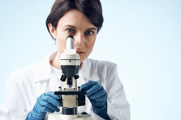 Médica sentada à mesa microscópio pesquisa biotecnologia luz de fundo