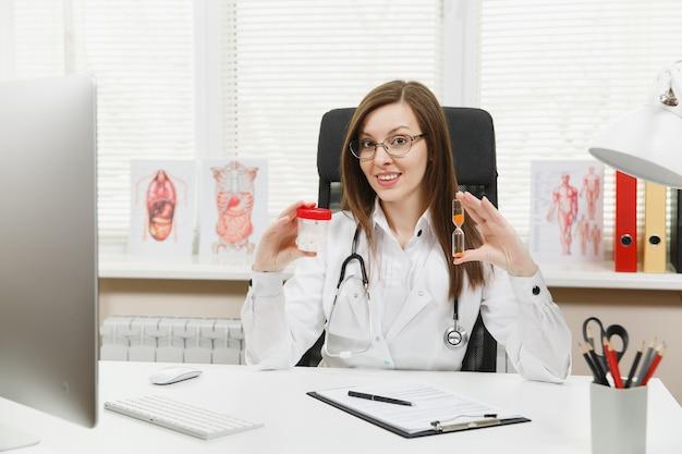 Médica sentada à mesa, segurando o frasco com comprimidos brancos, ampulheta, trabalhando com documentos médicos em um consultório no hospital