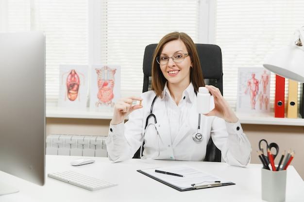Médica sentada à mesa, segurando um frasco com comprimidos brancos, trabalhando com documentos médicos em um consultório de hospital