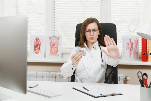 Médica sentada à mesa segurando um pacote de dólares em dinheiro, diga não ao suborno, mostrando um gesto de pare com a palma da mão no escritório no hospital