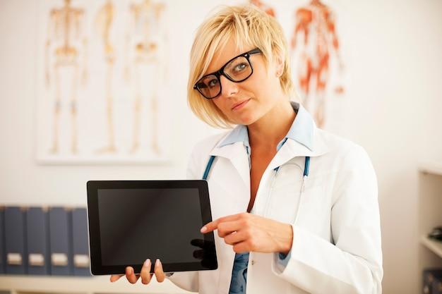 Médica séria apontando para tablet digital