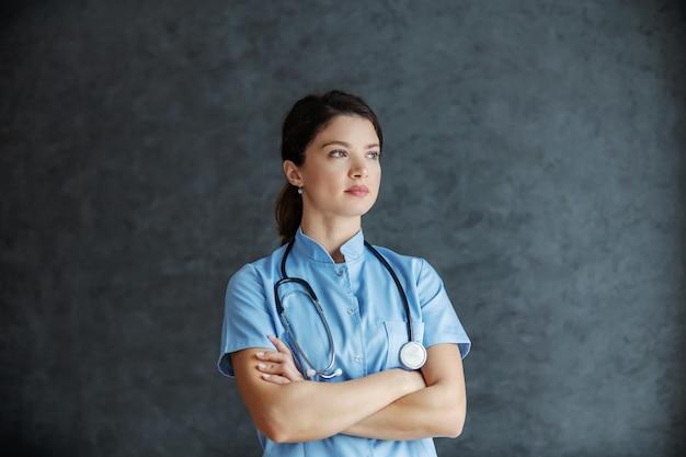 Médica séria com estetoscópio no pescoço em pé com os braços cruzados