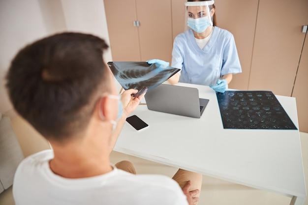 Médica séria oferecendo ao paciente para olhar a imagem do raio x
