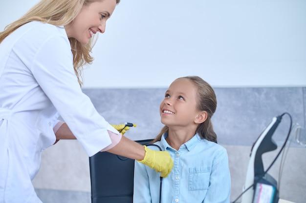 Médica simpática com luvas esterilizadas e jaleco preparando uma menina para um exame de audição
