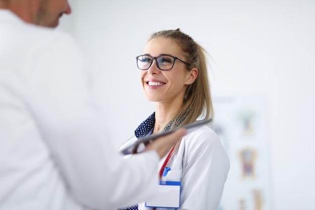 Médica sorri e se comunica com o colega.