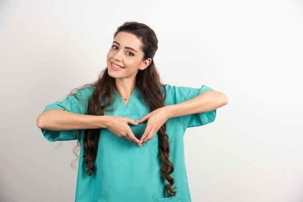 Médica sorridente de uniforme, mostrando a forma do coração das mãos.