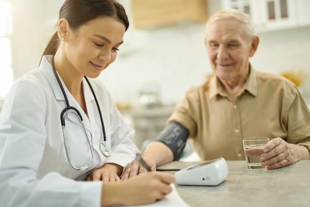Médica sorridente fazendo anotações enquanto examina o homem sênior sentado ao lado dela